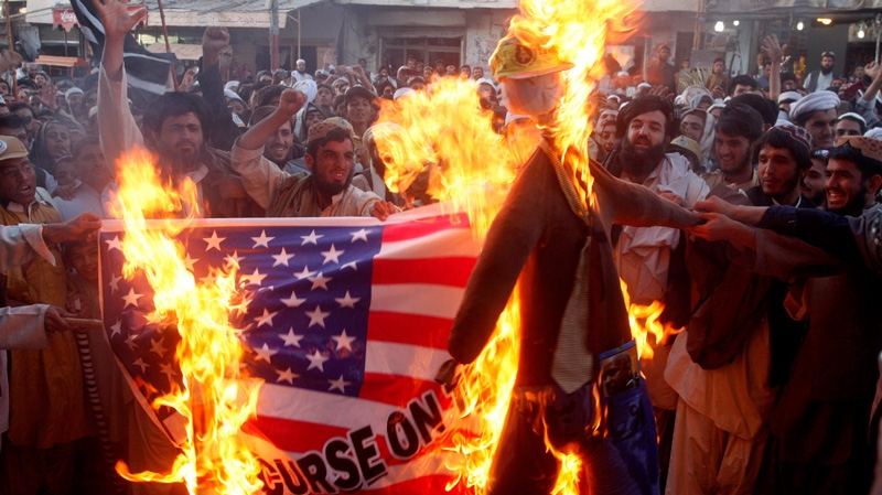In this Thursday, Sept. 20, 2012 file photo, Pakistani protesters burn a representation of a U.S. flag and an effigy of U.S. President Barack Obama in the Pakistani border town of Chaman along the Afghanistan border. (AP Photo/Matiullah Achakzai, File)