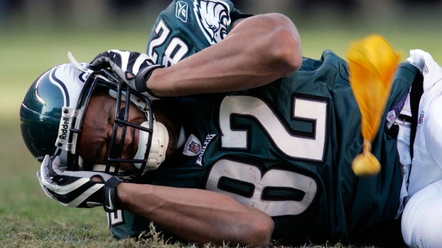 A NFL player lies on the field and holds his head after a hard hit, which caused him to suffer a concession, during the fourth quarter of a football game Sunday, Oct. 26, 2008. (AP / Mel Evans)