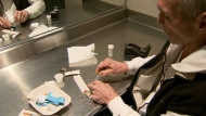 A man is seen holding a needle at a safe injection site in Vancouver in this undated image.