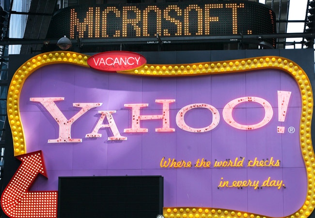 A Times Square news ticker flashes a headline about Microsoft above a billboard for Yahoo in New York. (AP / Mark Lennihan)