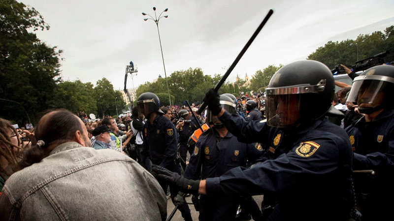 Spanish police in full riot gear confront demonstrators during a march to the parliament against austerity measures, announced by the Spanish government in Madrid, Spain, on Sept. 25, 2012. (AP/Daniel Ochoa De Olza)