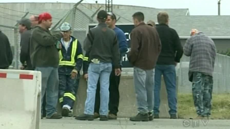 Workers are seen after an explosion at Irving Oil in Saint John, N.B., on Wednesday, Sept. 26, 2012.