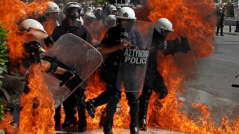 A fire bomb explodes among riot police during clashes in Athens, Wednesday, Sept. 26, 2012. (AP / Nikolas Giakoumidis)