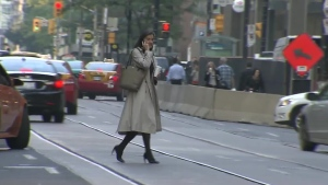 A pedestrian is seen jay walking while talking on a cell phone in downtown Toronto, Thursday, Sept. 27, 2012.