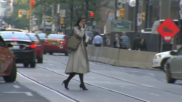 A pedestrian is seen jay walking while talking on a cell phone in downtown Toronto, Thursday, Sept.