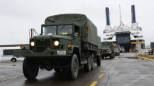 A convoy of military vehicles flow off the Joseph and Clara Smallwood ferry at Argentia, N.L., on Saturday, Sept. 25, 2010. (Jerry Kean / DND-HO-WO - THE CANADIAN PRESS)