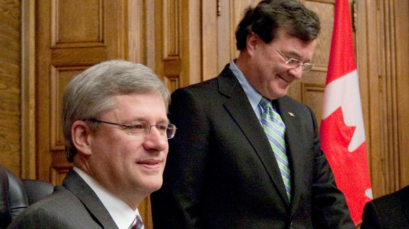 Minister of Finance Jim Flaherty looks on as Prime Minister Stephen Harper speaks about the Economic Action Plan during a photo op in his office on Parliament Hill in Ottawa, Monday, Sept. 27, 2010. (Adrian Wyld / THE CANADIAN PRESS)
