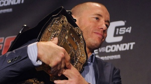 Defending UFC welterweight champion Georges St-Pierre carries his belt following a news conference in Montreal on Thursday, Sept. 27, 2012. (The Canadian Press/Ryan Remiorz)