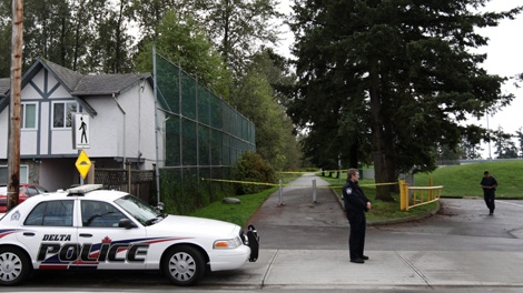 A police officer stands at the entrance to a pathway to a wooded area as other officers investigate the beating death of a 15-year-old girl at Mackie Park in Delta, B.C., on Sunday, Sept. 26, 2010. (CP/Darryl Dyck)