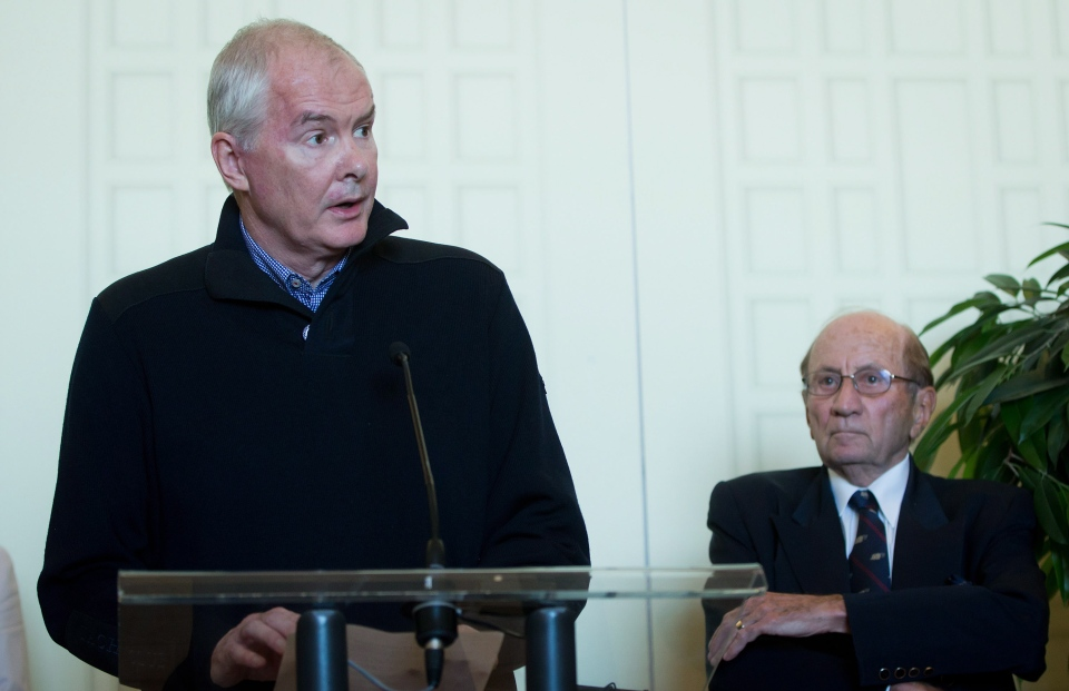 FILE - Former VANOC president and CEO John Furlong, left, reads a statement responding to allegations of abuse against Furlong brought forward by former First Nations students in Burns Lake dating back to 1969, as his lawyer Marvin Storrow listens during a news conference in Vancouver, on Thursday, Sept. 27, 2012. (Darryl Dyck / THE CANADIAN PRESS)