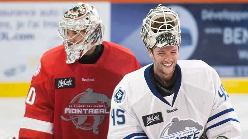 LA Kings goaltender Jonathan Bernier, right laughs with Chicago Blackhawks goalie Cory Crawford following a charity hockey game in Chateauguay, Que., Thursday, September 27, 2012. (THE CANADIAN PRESS/Graham Hughes.)