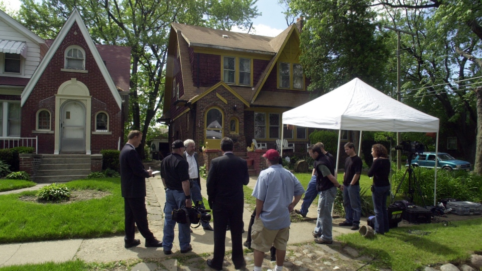 In this May 28, 2004, file photo, members of the media gather outside a Detroit home where investigators ripped up floorboards where one-time Jimmy Hoffa ally Frank Sheeran claims to have killed him. (AP Photo/Detroit News, Seth Lower)