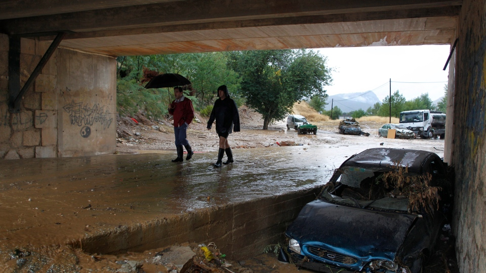 Residents walk by a wrecked car carried away by flash floods after heavy rain in the town of Villanueva del Rosario, Malaga, southern Spain, Friday, Sept. 28, 2012. (AP Photo/Sergio Torres)