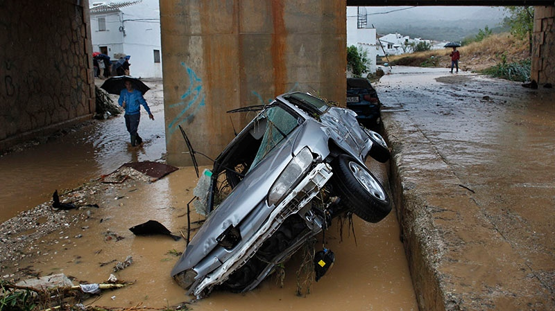 Residents walk by a wrecked car carried away by flash floods after heavy rain in the town of Villanueva del Rosario, Malaga, southern Spain, Friday, Sept. 28, 2012. (AP / Sergio Torres)