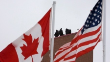 Security forces stand on the roof of the terminal building for the arrival of Barack Obama in Ottawa