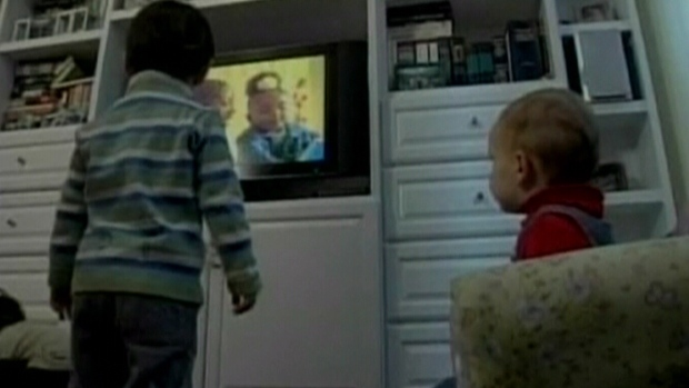 A pair of children are shown watching television.