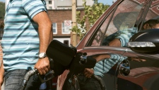 A motorist fills up at a gas station in Montreal on Wednesday, Sept. 12, 2012
