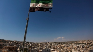 In this Tuesday, June 12, 2012 file photo, a Syrian revolutionary flag waves on top of a building on the outskirts of Aleppo, Syria.  (AP Photo/Khalil Hamra, File)