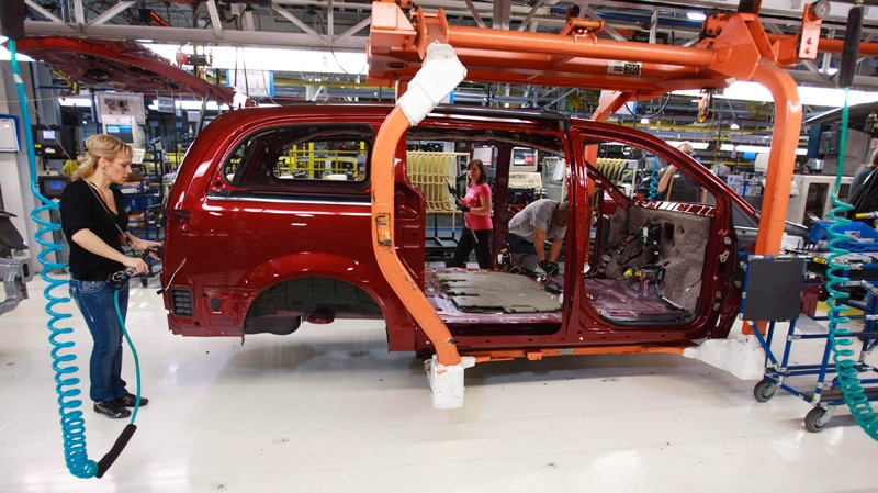 A worker on the production line at Chrysler's assembly plant in Windsor, Ontario, works on one of their new minivans on Jan. 18, 2011. (Geoff Robins / THE CANADIAN PRESS)