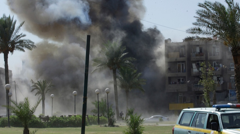 Plumes of smoke rise from the scene of a car bomb attack near the Sacred Heart Church in the Karrada neighborhood of Baghdad, Iraq, Sunday, Sept. 30, 2012. (AP / Khalid Mohammed)