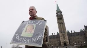 A lone anti-abortion protester spreads his message on Parliament Hill in Ottawa on Thursday, April 26, 2012. (THE CANADIAN PRESS/Sean Kilpatrick)