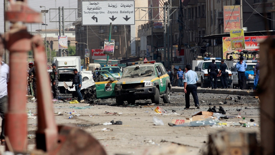 Iraqi policemen inspect the scene of a car bomb attack near the Sacred Heart Church in the Karrada Neighborhood of Baghdad, Iraq, Sunday, Sept. 30, 2012. (AP / Hadi Mizban)