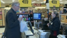 Alberta Agriculture Minister Verlyn Olson purchases ground beef at a Co-op store in Camrose, Alta