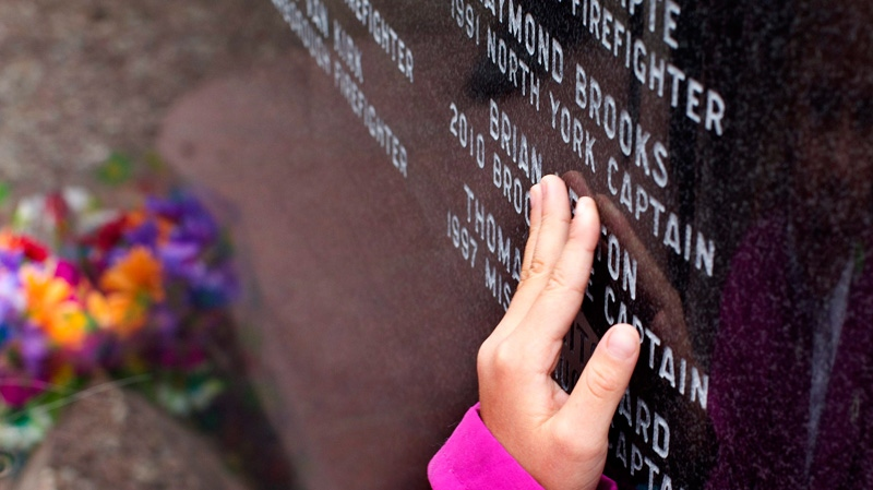 Kaityn Welsh, 5, trails her finger across the name of her grandfather on a monument to firefighters who have died on the job following a service to recognize the contributions and sacrifice of Ontario's firefighters at the Ontario Firefighters Memorial in Toronto on Sunday October 3, 2010. (THE CANADIAN PRESS/Chris Young)