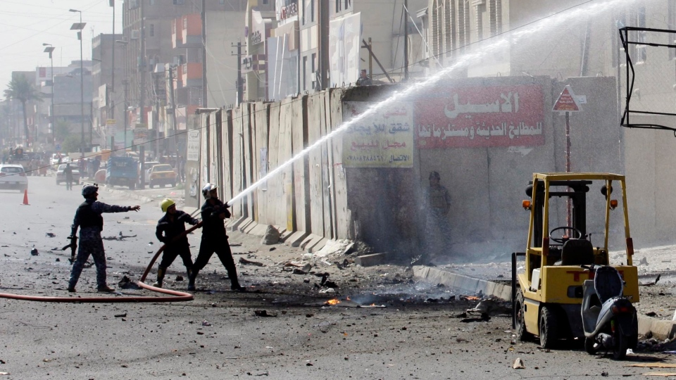 Iraqi firefighters extinguish a fire at the scene of a car bomb attack near the Sacred Heart Church in the Karrada Neighborhood of Baghdad, Iraq, Sunday, Sept. 30, 2012. (AP / Khalid Mohammed)