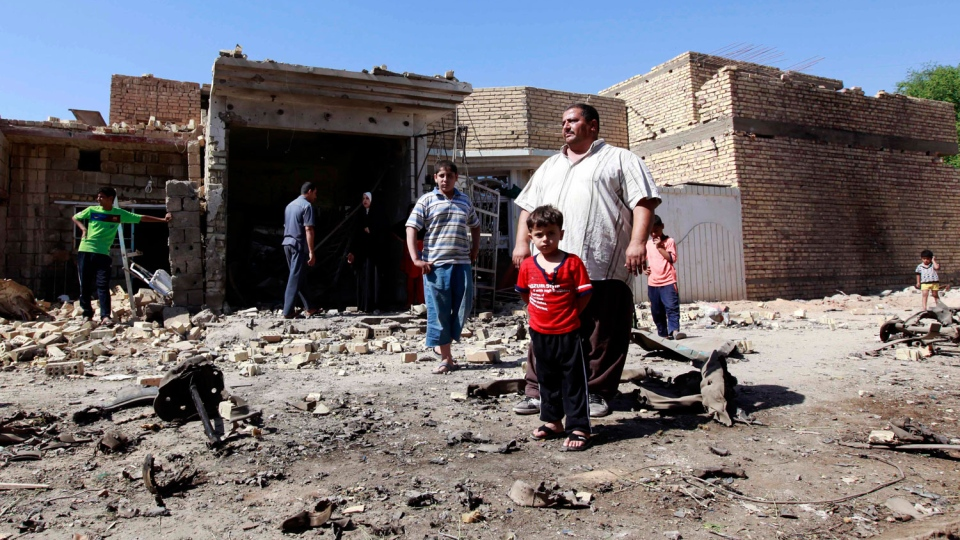 Iraqis stand in rubble at the scene of a car bomb attack in the town of Taji, about 12 miles (20 kilometers) north of Baghdad, Iraq, Sunday, Sept. 30, 2012. (AP / Hadi Mizban)