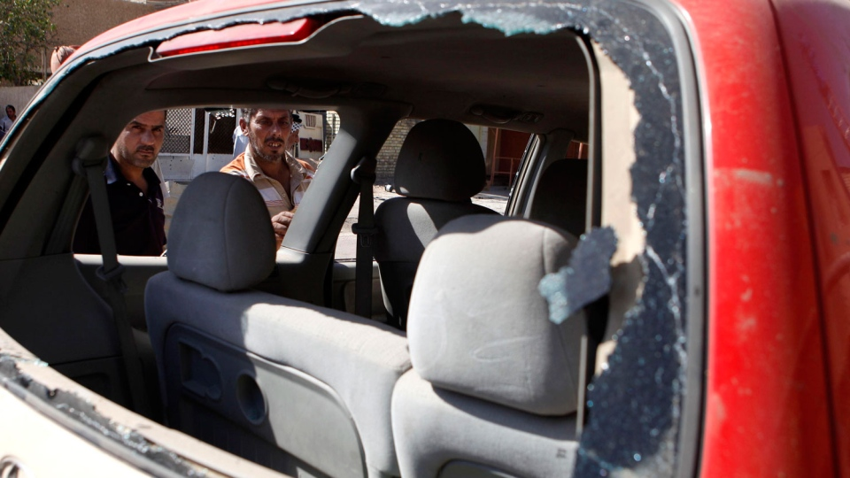 Iraqis inspect the scene of a car bomb attack in Baghdad, Iraq, Sunday, Sept. 30, 2012. (AP / Karim Kadim)