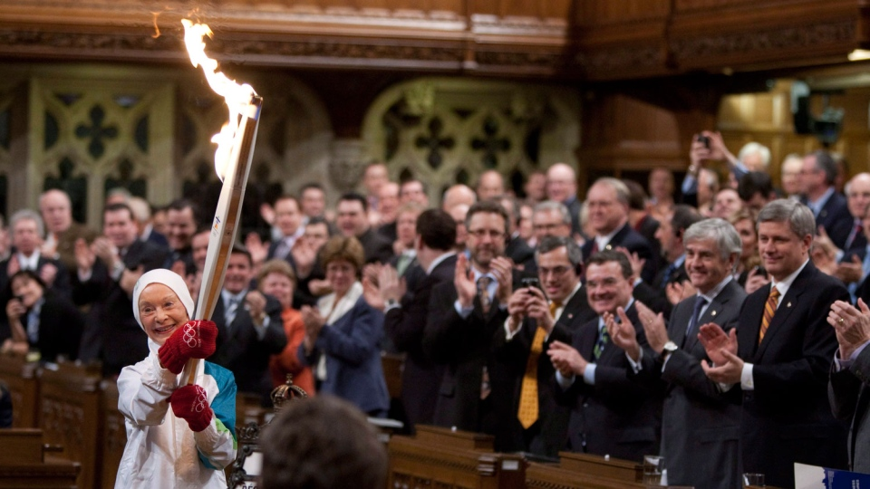 Former Canadian Olympic figure skater Barbara Ann Scott carries the Olympic torch into the House of Commons during a ceremony on Parliament Hill in Ottawa, Thursday December 10, 2009. (Sean Kilpatrick/THE CANADIAN PRESS)