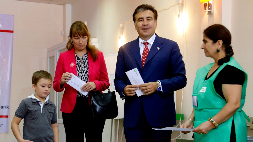 Georgian President Mikhail Saakashvili, second right, his wife Sandra Roelofs, second left, and his son Nikoloz, left, stand around a ballot box before voting at a polling station in Tbilisi, Georgia, Monday, Oct. 1, 2012. (AP / Efrem Lukatsky)
