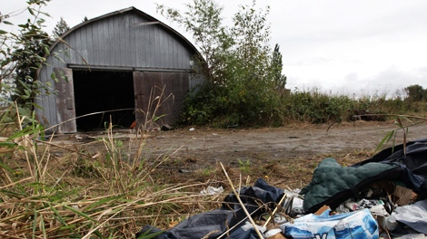 A sleeping bag and an empty case of beer sit near a structure on a property where a 16-year-old girl was allegedly drugged and gang raped during a rave party in Pitt Meadows, B.C., on Saturday September 18, 2010. (CP/Darryl Dyck)