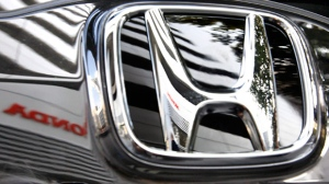 Honda Motor Co.'s headquarter building is reflected on Honda's car logo in Tokyo, Japan, Jan. 21, 2010. (AP / Shizuo Kambayashi)
