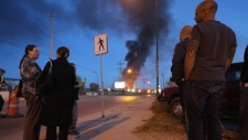 Onlookers watch from a distance as a fire burns at Speedway International, a methanol fuel plant in