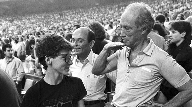 Former prime minister Pierre Trudeau shows how tall his eldest son Justin has grown in relation to himself during the seventh inning stretch at the Montreal Expos game in Montreal on April 20, 1987. Justin Trudeau may seem to be following in dad's footsteps as he prepares to seek the Liberal leadership, but he's really heading down a vastly different path into unknown territory. (Paul Chiasson / THE CANADIAN PRESS)