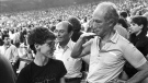 Former prime minister Pierre Trudeau shows how tall his eldest son Justin has grown in relation to himself during the seventh inning stretch at the Montreal Expos game in Montreal on April 20, 1987. (Paul Chiasson / THE CANADIAN PRESS)