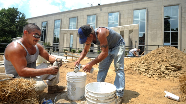 Workers mix cement to set handrails on a new wheelchair ramp in Owensboro on June 25, 2012.