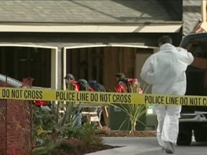 Police investigators can be seen outside the home in the Gordon Head, B.C. neighbourhood where the victim's body was found.