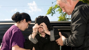 """Melissa Ann Weeks, 77, of New Glasgow, N.S., also known as the """"Internet Black Widow,"""" leaves a Cape Breton Regional Police Services vehicle escorted by Const. Erin Donovan, left, and Const.Geoff MacLeod for a court appearance at the Sydney Justice Centre on Tuesday, Oct.2, 2012. (Vaughan Merchant / THE CANADIAN PRESS)"""