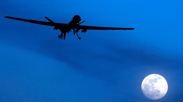 A U.S. Predator drone flies over the moon above Kandahar Air Field, southern Afghanistan on Jan. 31, 2010. (AP / Kirsty Wigglesworth)