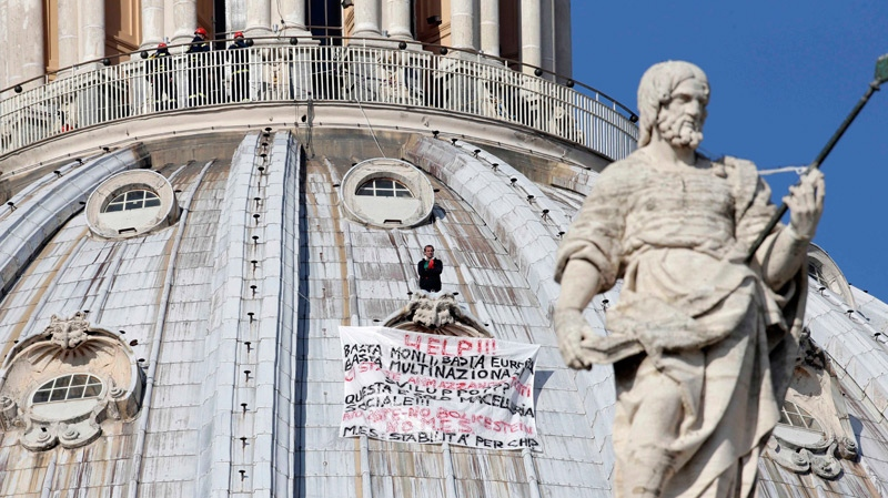 Firefighters look at Italian businessman Marcello di Finizio standing above his banner as he protests on St. Peter's dome, at the Vatican, Wednesday, Oct. 3, 2012. (AP / Andrew Medichini)