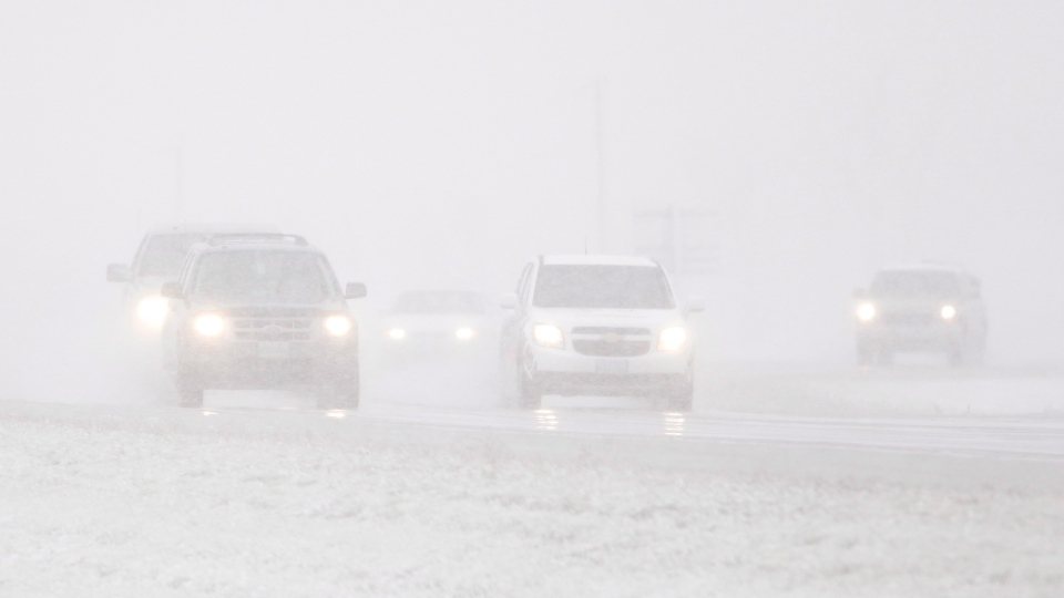Drivers make their way through near whiteout conditions on Highway 12, just north of Steinbach and 70 kilometres southeast of Winnipeg, as an early snowstorm unexpectedly hit the province, Thursday, Oct.4, 2012. (John Woods / THE CANADIAN PRESS)