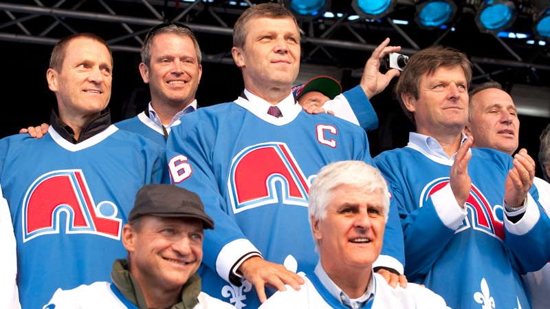 """Former Quebec Nordiques players pose together after they were introduced to a crowd of over 60,000 people on the Plains of Abraham in a gathering called """"La Marche Bleue"""" asking for a comeback of an NHL team and a new arena in Quebec City, Saturday, October 2, 2010. (Jacques Boissinot / THE CANADIAN PRESS)"""