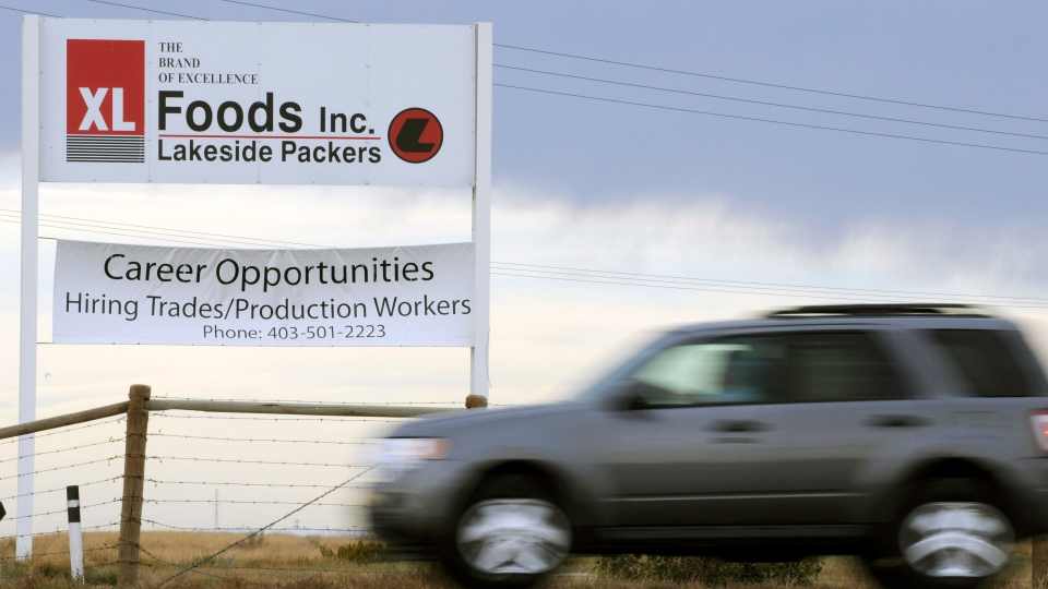 A vehicle passes the main entrance sign leaving XL Foods' Lakeside Packers plant at Brooks, Alta. on Monday, Oct. 1, 2012, 2012. (Larry MacDougal / THE CANADIAN PRESS)