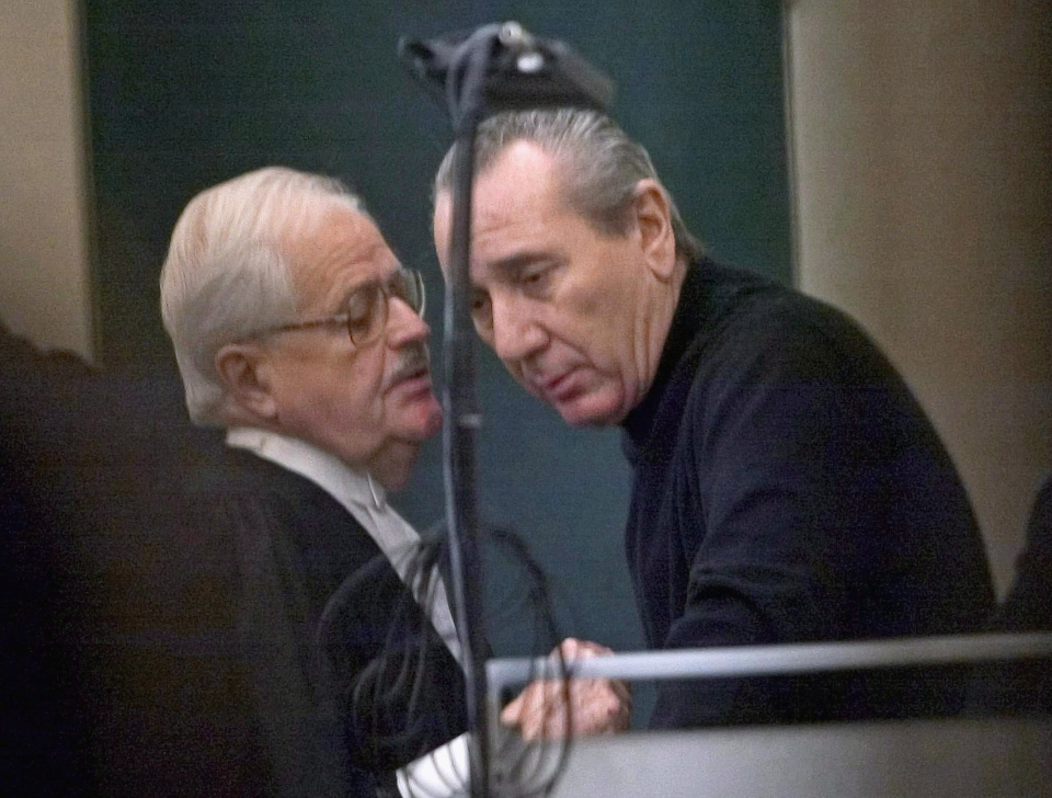Vito Rizzuto, right, reputed head of the Montreal Mafia, speaks with his attorney Jean Salois after his hearing in Montreal on Feb. 6, 2004. (Ryan Remiorz / THE CANADIAN PRESS)