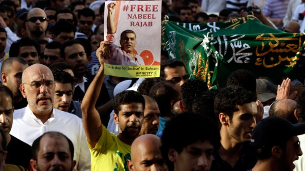 A Bahraini man holds up a sign calling for the release of human rights activist Nabeel Rajab during the funeral procession for Rajab's elderly mother in Manama, Bahrain, on Thursday, Oct. 4, 2012. (AP / Hasan Jamali)