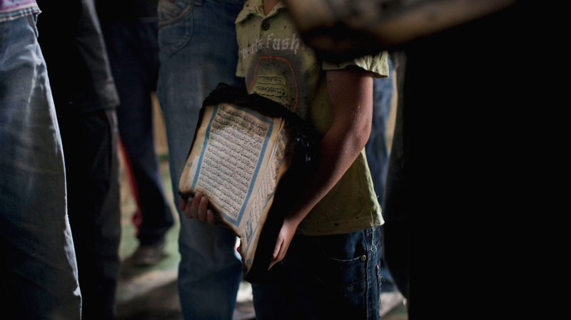 A Palestinian child holds a charred Quran, a Muslim holy book, inside a mosque in the West Bank village of Beit Fajjar, near Bethlehem, Monday Oct. 4, 2010. (AP / Bernat Armangue)