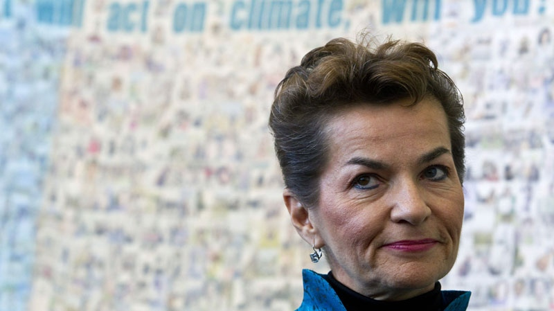 UN climate chief Christiana Figueres stands in front of a poster made by Green Peace before the opening of the United Nations Climate Change Conference in Tianjin, China, Monday, Oct. 4, 2010. (AP Photo/Alexander F. Yuan)